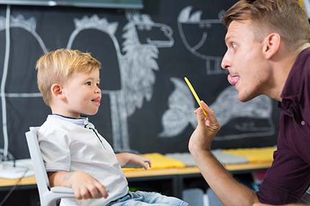 Speech therapist using various techniques to help a young patient